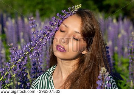 Gorgeous Beautiful Girl Eyes Closed Leaned Lupine Flower To Her Face On Blooming Meadow, Merging Wit
