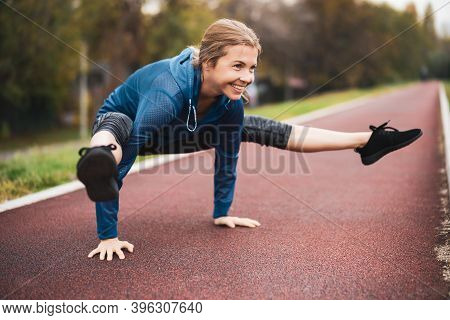 Beautiful Adult Woman Is Exercising Outdoor On Cloudy Day In Autumn. Tittibhasana / Insect / Firefly