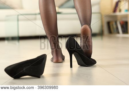 Back View Close Up Of Woman Arriving Home After Work Undressing Taking Off Shoes