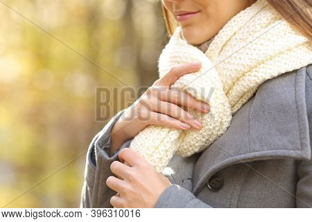 Close Up Of Woman Hands Putting On A Scarf In A Park In Winter