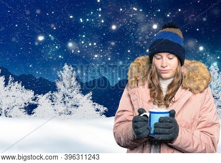 Young Woman In Winter Clothes Warms Her Hands On A Hot Mug In Wintry Landscape
