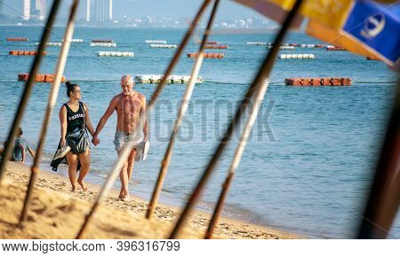 Pattaya, Thailand - November 11: Unnamed Couple Takes A Romantic Walk Holding Hands Down Jomtien Bea