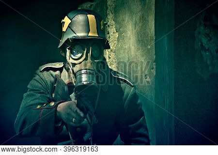 World War 2 Soldier In A Gas Mask Aims His Gun. War Concept.