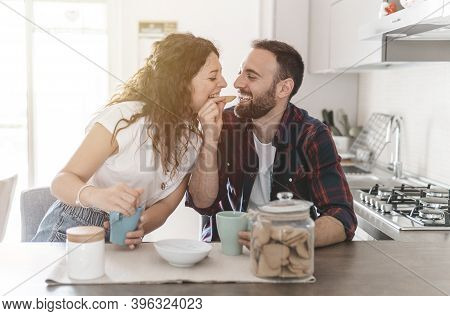 Young Couple Laughs And Jokes While Sitting On The Floor Browsing And Shopping Online With Laptop -