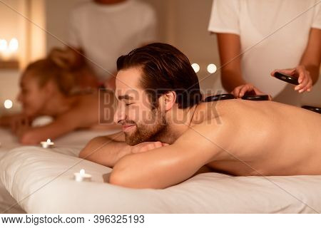 Couples Massage. Happy Relaxed Man And Woman At Spa Salon Lying With Hot Stones On Back Enjoying Rel