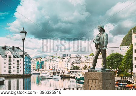 Alesund, Norway. Statue Of Young Sailor-fisher Boy On Brosundet Canal. Old Wooden Houses In Summer D