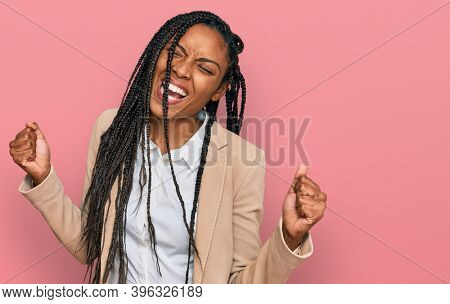 African american woman wearing business jacket very happy and excited doing winner gesture with arms raised, smiling and screaming for success. celebration concept.