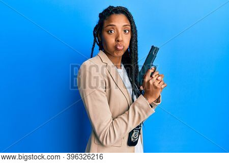 African american police woman holding gun puffing cheeks with funny face. mouth inflated with air, catching air.
