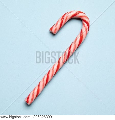 Rd and white candy cane on light blue background, square crop