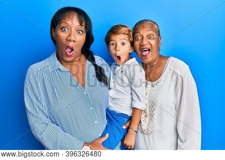Hispanic family of grandmother, mother and son hugging together scared and amazed with open mouth for surprise, disbelief face