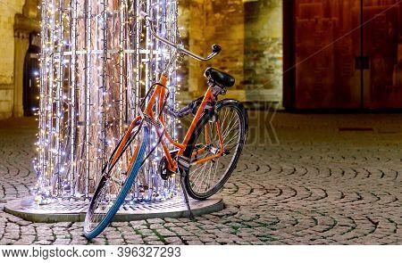 Bicycle At Traditional European Christmas Market At Night. Garland Of Glowing Lanterns Adorns Tree N