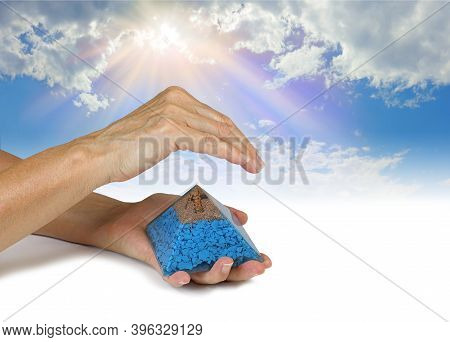 Sensing Orgone Pyramid Resonance On  Blue Sky Background - Female Holding An Orgone Pyramid In Left