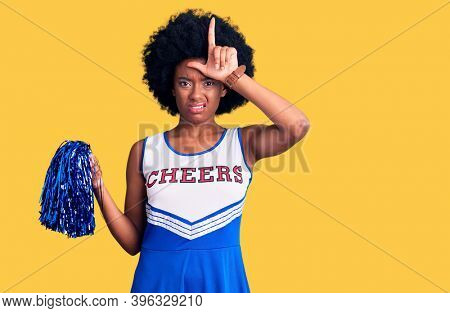 Young african american woman wearing cheerleader uniform holding pompom making fun of people with fingers on forehead doing loser gesture mocking and insulting.