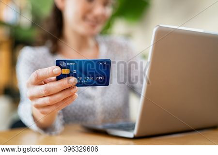 Close up hand of young woman holding credit card while making online payment. Woman hands holding a debit card and using laptop to do shopping online. Smiling girl with bank card paying bills online.