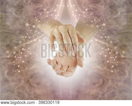 Shamanic Energy Healer Sending Healing -  Female Healer With Cupped Hands Against A Gently Sparkling