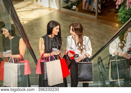 Two Girlfriends Going Up The Escalator With Shopping Bags And Talking In The Shopping Mall