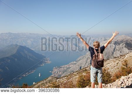 Traveler With Backpack On Mountain Top. Happy Man With Raised Arms In Autumn Landscape. Tourist Enjo