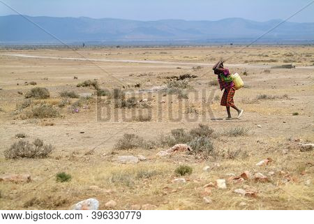 A Local Woman In Bright Clothes Carries A Heavy Load Against The Backdrop Of An African Landscape. K