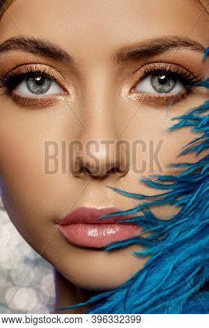 Beauty fashion model face and feathers. Beautiful female face. Girl with perfect fresh skin. Luxurious lady. Makeup and vogue.