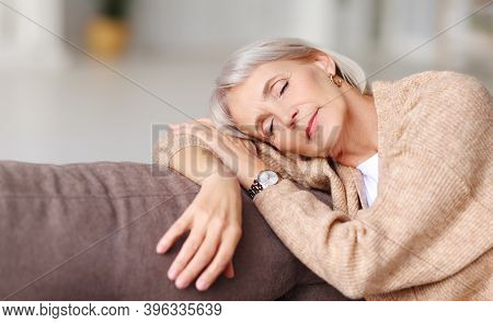 Relaxed Middle Aged Female Leaning On Hand And Having Sweet Daytime Nap On Soft Couch At Home