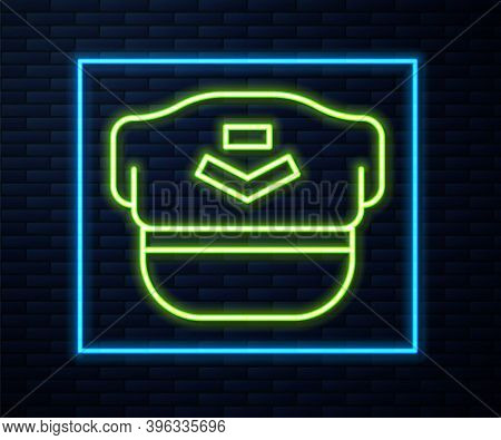 Glowing Neon Line Pilot Hat Icon Isolated On Brick Wall Background. Vector