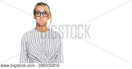 Beautiful blonde woman wearing business shirt and glasses puffing cheeks with funny face. mouth inflated with air, crazy expression.