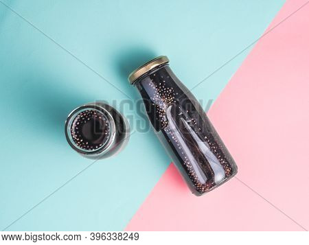 Detox Activated Charcoal Black Chia Water Or Mocktail On Colorful Blue And Pink Background.two Bottl