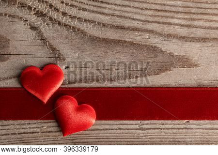 Valentine's day two red silk hearts and ribbon stripe on wooden background, love concept