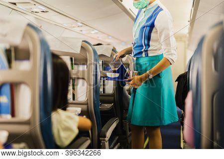Flight Attendant In Facial Mask Protection From Covid-19 Serves Passengers A Coffee.