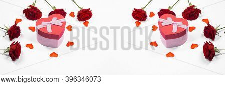 Beautiful gift in heart shaped box with ribbon bow rose flowers and paper hearts isolated on white background