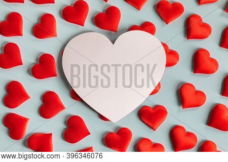 Valentine's day many red silk hearts and white heart shaped card on blue background, love concept