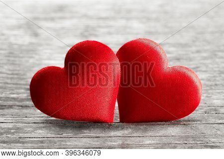 Valentine's day two red silk hearts on wooden background, love concept