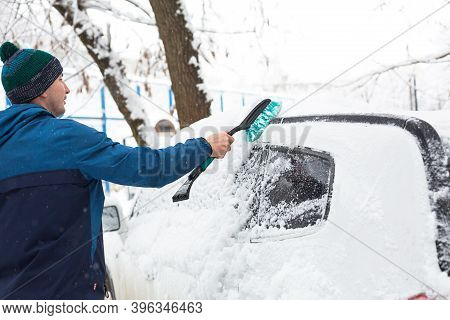 A Man Brushes Snow From A Car After A Snowfall. A Hand In A Blue Jacket With A Car Broom On The Whit