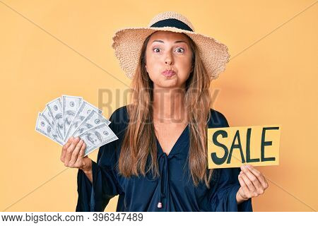 Middle age hispanic woman wearing summer hat holding sale banner and dollars puffing cheeks with funny face. mouth inflated with air, catching air.