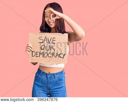 Young beautiful chinese girl holding save our democracy protest banner smiling happy doing ok sign with hand on eye looking through fingers