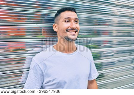 Young hispanic man smiling happy leaning on the wall at street of city.