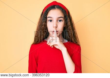 Cute hispanic child girl wearing casual clothes and diadem asking to be quiet with finger on lips. silence and secret concept.