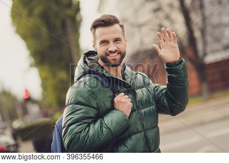 Photo Of Cheerful Toothy Beaming Young Guy Dressed Green Coat Rucksack Walking Waving Arm Outdoors U