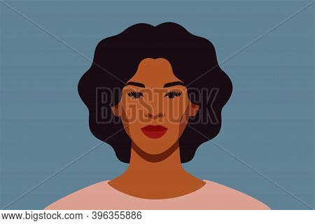Strong Black Woman With Curly Hair Smiles And Looks Directly. Confident Young Woman With Brown Skin