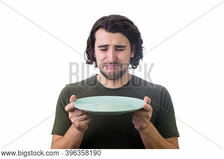 Desperate Man Crying As Looks At An Empty Dish Plate In His Hands, Isolated On White Background. Dis