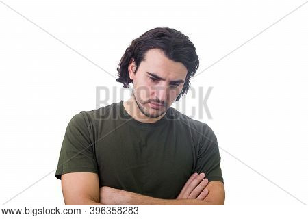 Disappointed And Annoyed Young Man Makes A Displeased Facial Expression, Arms Crossed Looking Down,