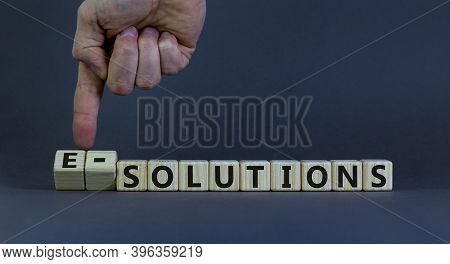 Time To E-solutions. Male Hand Flips Wooden Cubes And Changes The Word 'solutions' To 'e-solutions'.