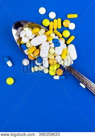Pills In The Spoon On The Blue Background Closeup