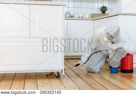 A Man In A Protective Suit With A Disinfectant Spray To Disinfect Household Items And Furniture. The