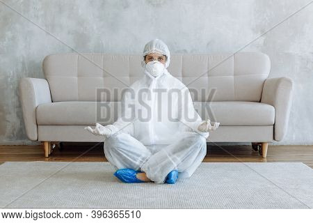 A Woman In A Protective Suit For Disinfecting Household Items And Furniture Is Meditating In A Room.