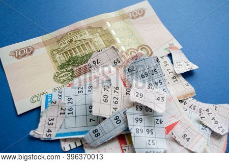 Moscow, Russia, July 2020: Torn Lottery Tickets With Numbers With Banknote Of One Hundred Rubles On