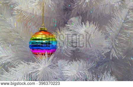 Bright Glass Rainbow Colored Christmas Ball, Bauble Hanging On A White Artificial Christmas Tree. Th