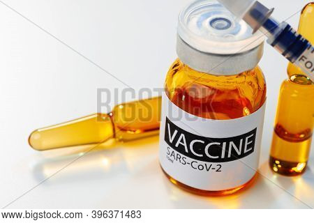 Sars-cov-2 Vaccine Vial And Syringe On White Table