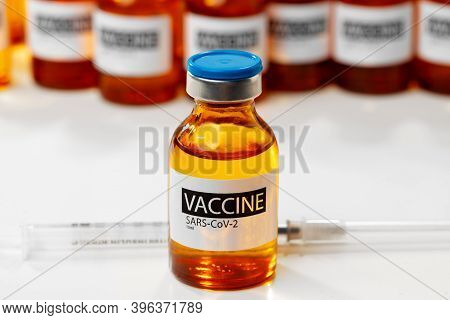 Sars-cov-2 Vaccine Vials And Syringe On White Background