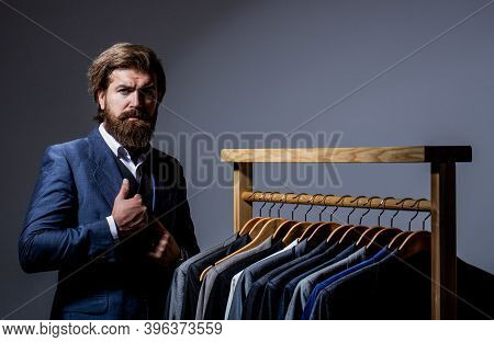 Male Suits Hanging In A Row. Men Clothing, Boutiques. Tailor, Tailoring. Stylish Mens Suit. Man Suit